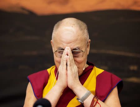 Exiled Tibetan spiritual leader, the Dalai Lama, gives a gesture of greeting as he arrives at a news conference in Copenhagen
