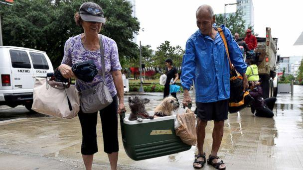 PHOTO: A couple of evacuees carry their dogs into the the George R. Brown Convention Center after Hurricane Harvey inundated the Texas Gulf coast with rain causing widespread flooding, in Houston, Aug. 27, 2017.  (Nick Oxford/Reuters)
