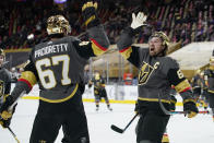 Vegas Golden Knights right wing Mark Stone, right, celebrates after left wing Max Pacioretty, left, scored against the Minnesota Wild during overtime of an NHL hockey game Monday, March 1, 2021, in Las Vegas. (AP Photo/John Locher)
