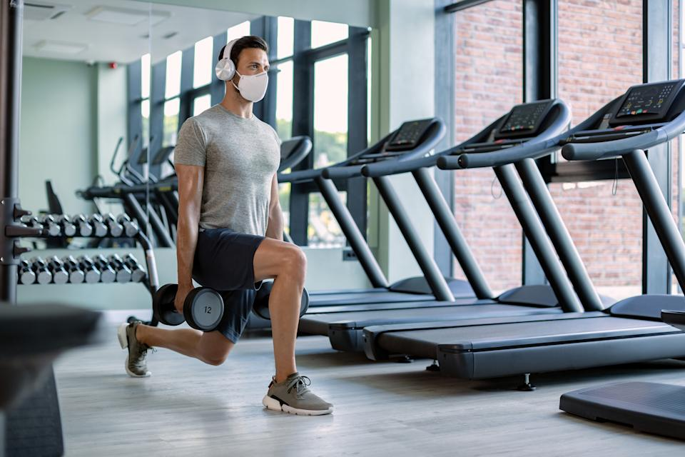 Male athlete exercising with hand weights in lunge position while wearing protective face mask in health club.