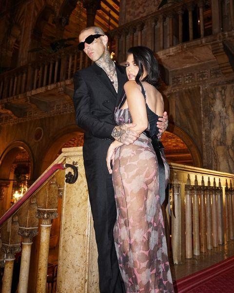 """<p>For Dolce & Gabbana's recent Alta Moda show in Venice, Kourtney Kardashian wears a sheer naked dress by the brand, accessorised with a floral belt, worn over black lingerie while standing alongside <a href=""""https://www.cosmopolitan.com/uk/entertainment/a35425919/kourtney-kardashian-travis-barker-dating-history/"""" rel=""""nofollow noopener"""" target=""""_blank"""" data-ylk=""""slk:Travis Barker"""" class=""""link rapid-noclick-resp"""">Travis Barker</a>. Barker commented on Kourtney's Instagram post """"We're moving to Italy"""" - so it sounds like they both enjoyed themselves.</p><p><a href=""""https://www.instagram.com/p/CTM8b-qokQ1/"""" rel=""""nofollow noopener"""" target=""""_blank"""" data-ylk=""""slk:See the original post on Instagram"""" class=""""link rapid-noclick-resp"""">See the original post on Instagram</a></p>"""