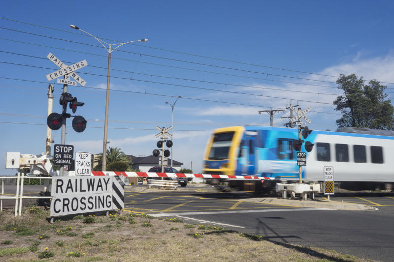 A commuter train passes through a railway level crossing on Eel Race Road, Seaford, Melbourne.
