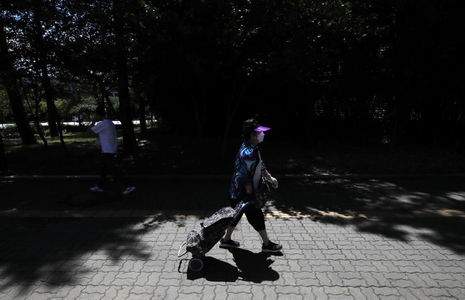 A woman wearing a face mask to help protect against the spread of the new coronavirus pulls her shopping cart in Seoul, South Korea, Wednesday, July 15, 2020. (AP Photo/Lee Jin-man)