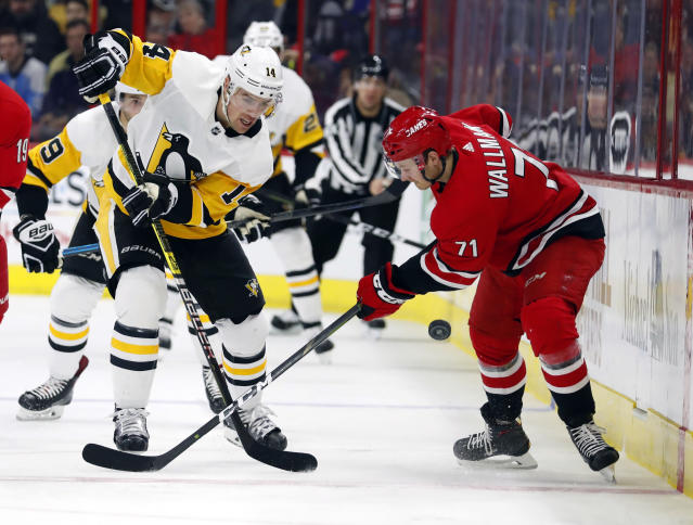 Pittsburgh Penguins' Tanner Pearson (14) wins the battle with Lucas Wallmark (71) during the second period of an NHL hockey game, Saturday, Dec. 22, 2018, in Raleigh, N.C. (AP Photo/Karl B DeBlaker)