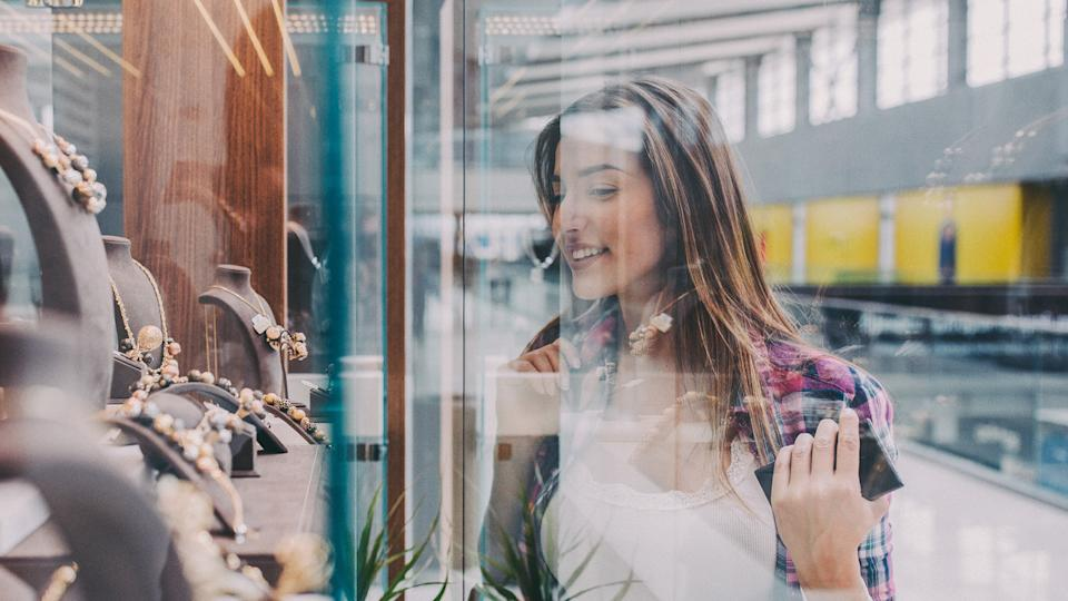 Young woman in the shopping mall looking at gorgeous jewellery on the shop window.