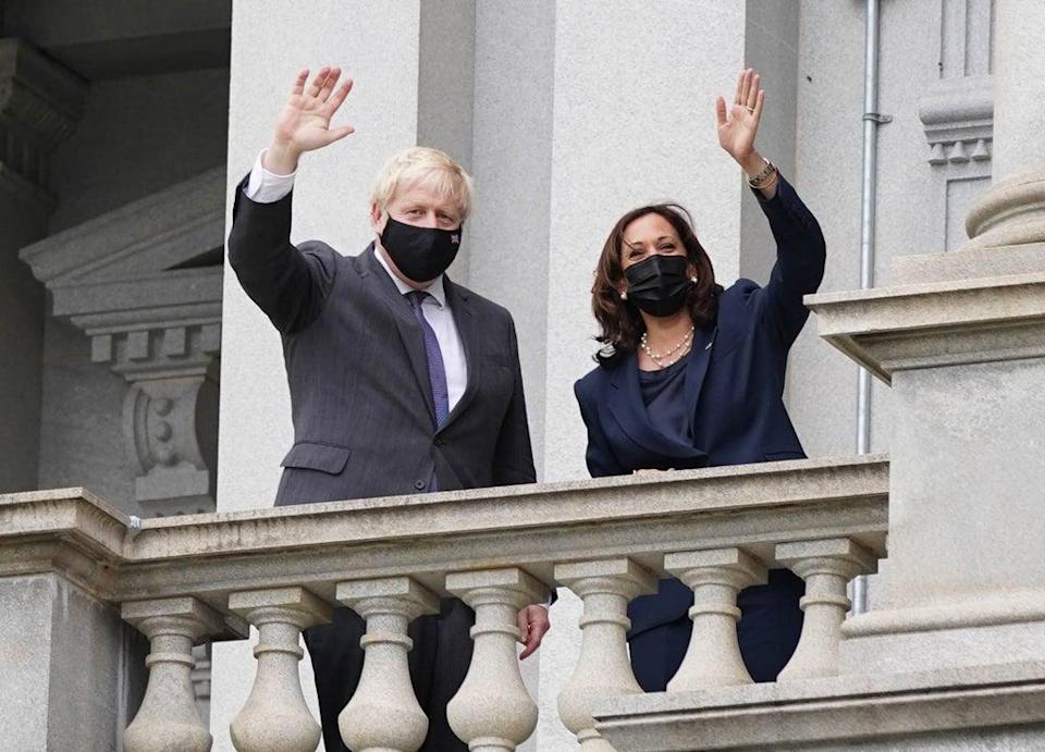 Boris Johnson and vice president Kamala Harris wave from a balcony of the Eisenhower Executive Office Building (Stefan Rousseau/PA) (PA Wire)