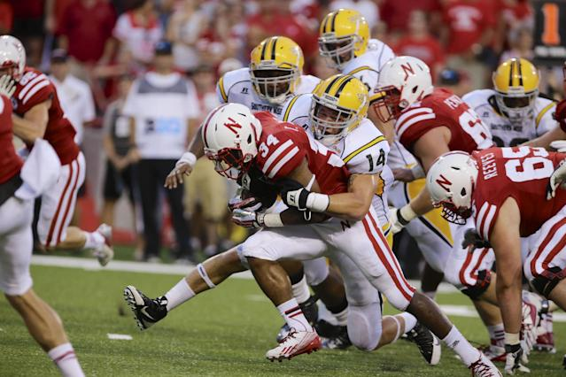 In this photo taken Sept. 7, 2013, Nebraska running back Terrell Newby (34) is tackled by Southern Mississippi linebacker Terrick Wright (14) in the second half of an NCAA college football game in Lincoln, Neb. Newby, who has always worn Payton's No. 34 and resembles his idol with his 5-foot-10, 185-pound frame, is part of the Huskers' three-back rotation along with Ameer Abdullah and Imani Cross. (AP Photo/Nati Harnik)
