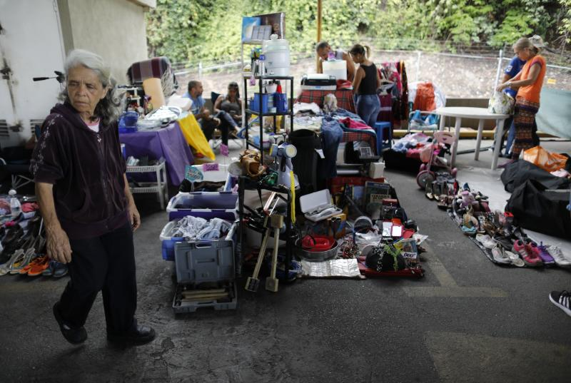 In this Sept. 29, 2019 photo, a woman walks through a secondhand market in Caracas, Venezuela. Residents across Venezuela have increasingly turned to second-hand street markets as migration continues unabated, some that pop up on Sundays or get organized through social media. (AP Photo/Ariana Cubillos)