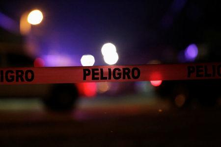 """FILE PHOTO - Police cordon reading """"Danger"""" is pictured at a crime scene where unknown assailants gunned down people at a garage in Ciudad Juarez"""