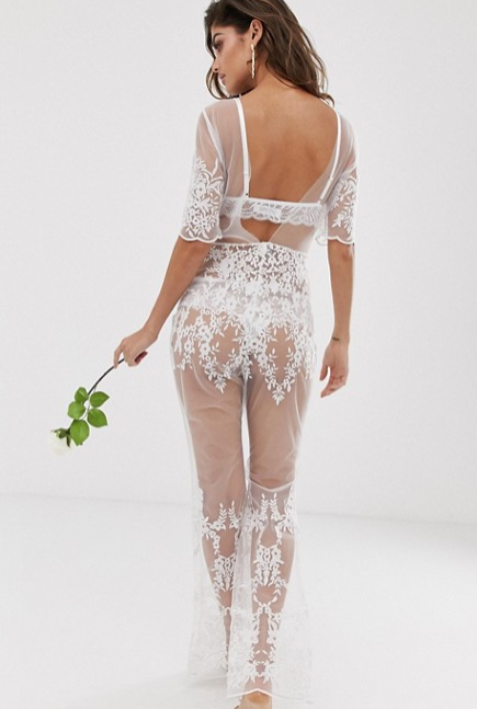 A photo of a model wearing ASOS's white see-through lace bridal jumpsuit.