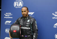 Mercedes driver Lewis Hamilton of Britain, with his award for winning pole position after the end of qualifying for Sunday's Formula One Turkish Grand Prix at the Intercity Istanbul Park circuit in Istanbul, Turkey, Saturday, Oct. 9, 2021. Hamilton who took pole position will start 10th due to a penalty with Mercedes driver Valtteri Bottas of Finland who came second promoted to pole, for the race. (Umit Bektas/Pool Photo via AP)