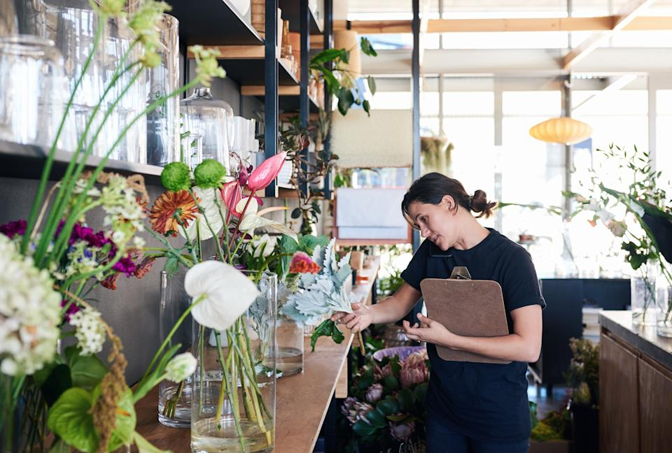 Young female florist talking on the phone with a customer and carrying a clipboard while working in her flower shop