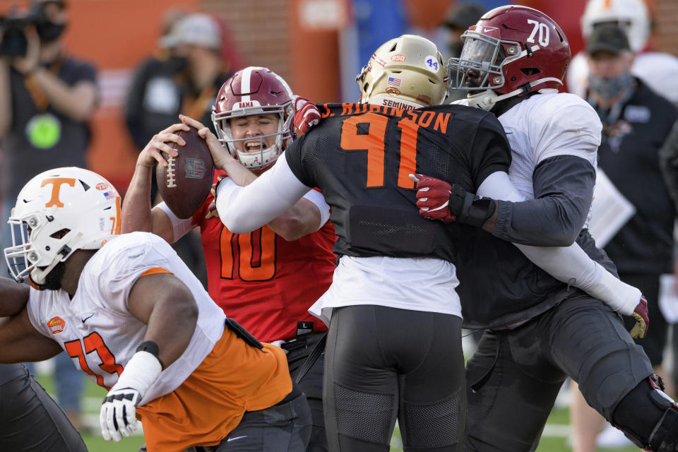 American Team quarterback Mac Jones of Alabama (10) gets tangled up with American Team Janarius Robinson of Florida State (91) during the American Team practice for the NCAA Senior Bowl college football game in Mobile, Ala. Wednesday, Jan. 27, 2021. (AP Photo/Matthew Hinton)