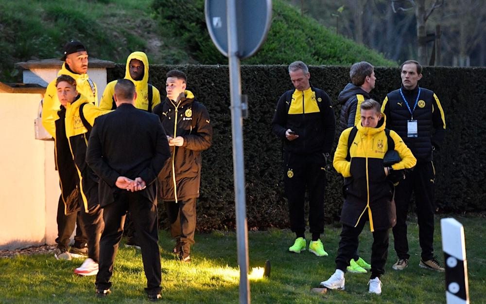Head coach Thomas Tuchel, right, and players of Borussia Dortmund stand outside their team bus after it was damaged in an explosion before the Champions League quarterfinal - Credit: AP