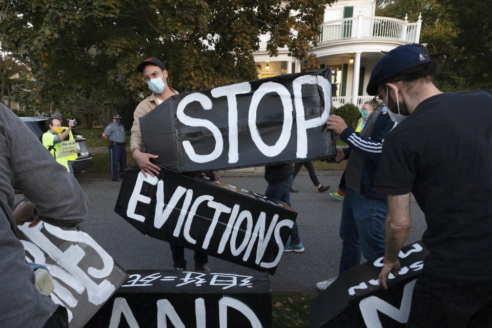 FILE - In this Oct. 14, 2020, file photo, housing activists erect a sign in front of Massachusetts Gov. Charlie Baker's house in Swampscott, Mass. The Justice Department said Saturday, Feb. 27, 2021 it will appeal a judge's ruling that found the federal government's eviction moratorium was unconstitutional. Prosecutors filed a notice in the case on Saturday evening, saying that it was appealing the matter the to the U.S. Court of Appeals for the Fifth Circuit. (AP Photo/Michael Dwyer, File)