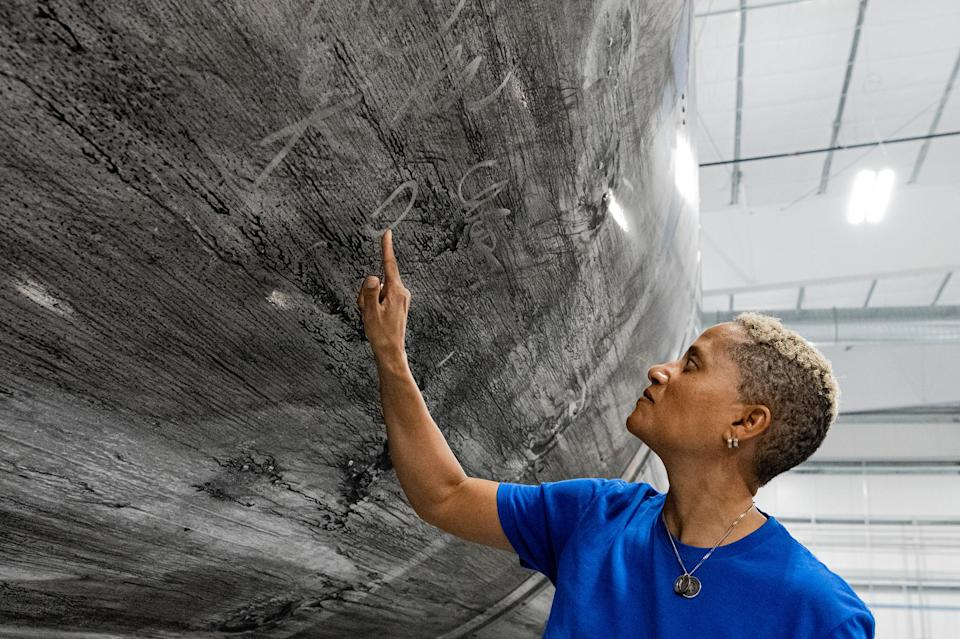 """Dr. Sian Proctor signing the Falcon 9 reusable rocket booster that will launch the Inspiration4 crew into space. It has become a new tradition for SpaceX crews to sign their reusable vehicles.<span class=""""copyright"""">John Kraus—Inspiration4</span>"""