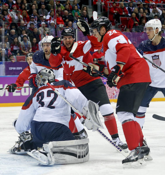 Canada forward Benn Jamie, center, reacts after scoring a goal against the USA during the second period of a men's semifinal ice hockey game at the 2014 Winter Olympics, Friday, Feb. 21, 2014, in Sochi, Russia. (AP Photo/Julio Cortez)
