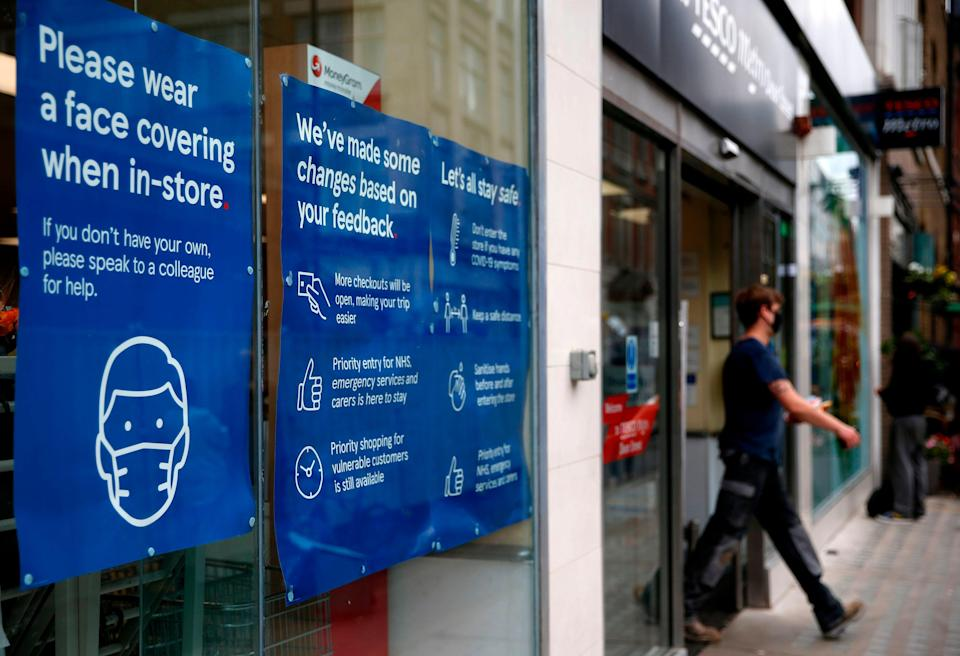 A Tesco store displays requests for shoppers to use face coverings (AFP via Getty Images)