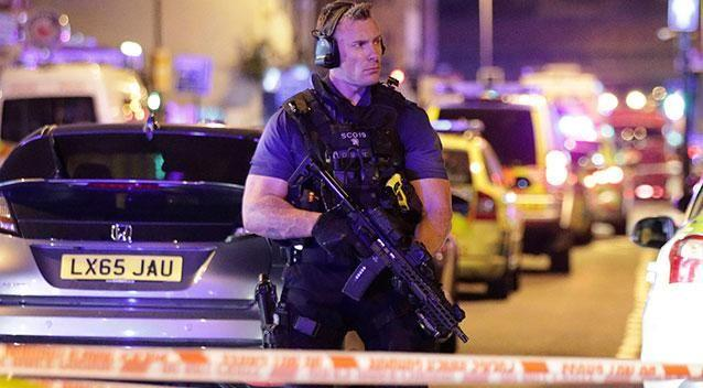 An armed police officer mans a cordon on the Seven Sisters Road at Finsbury Park. Photo: AP