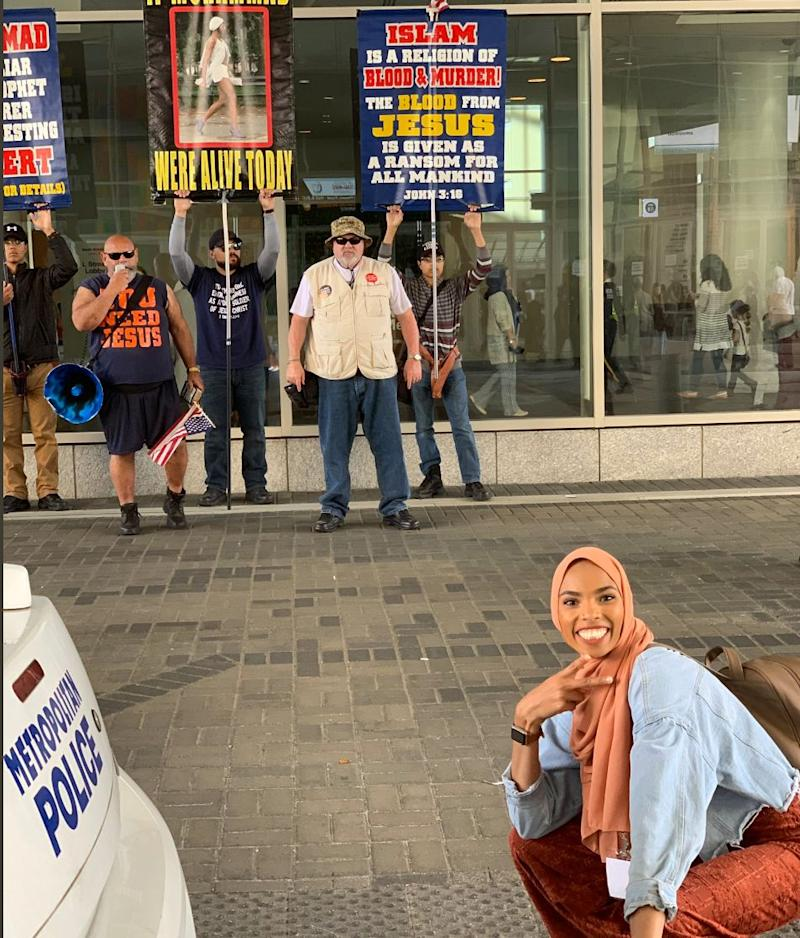 Muslim woman takes smiling photo in front of anti-Muslim protesters