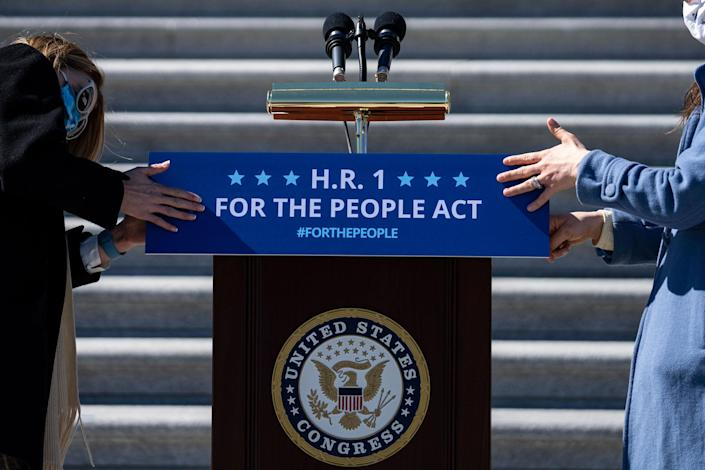Staffers place a sign on a podium in preparation for a news conference with House Democrats regarding H.R. 1, the For the People Act, on Capitol Hill on March 3, 2021.