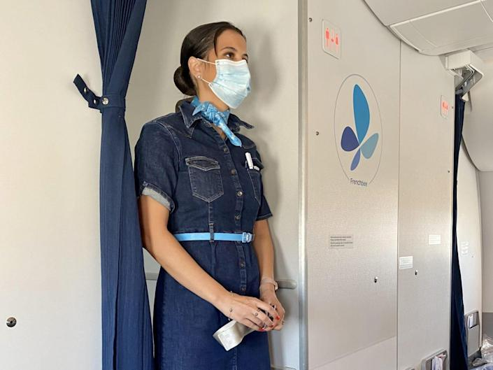 Frenchbee flight attendant wearing a surgical mask onboard
