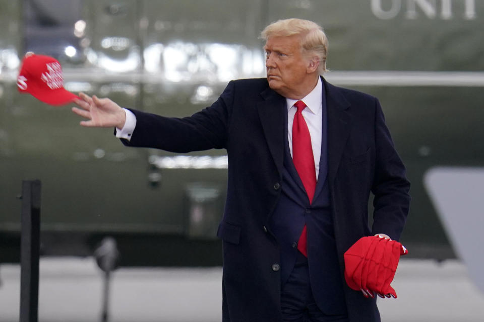 Supporters cheer as President Donald Trump tosses ball caps as he arrives for a campaign rally at the Altoona-Blair County Airport in Martinsburg, Pa, Monday, Oct. 26, 2020. (AP Photo/Gene J. Puskar)