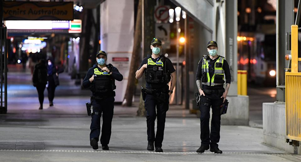 Three police officers, wearing masks, shown patrolling Melbourne streets. Source: AAP