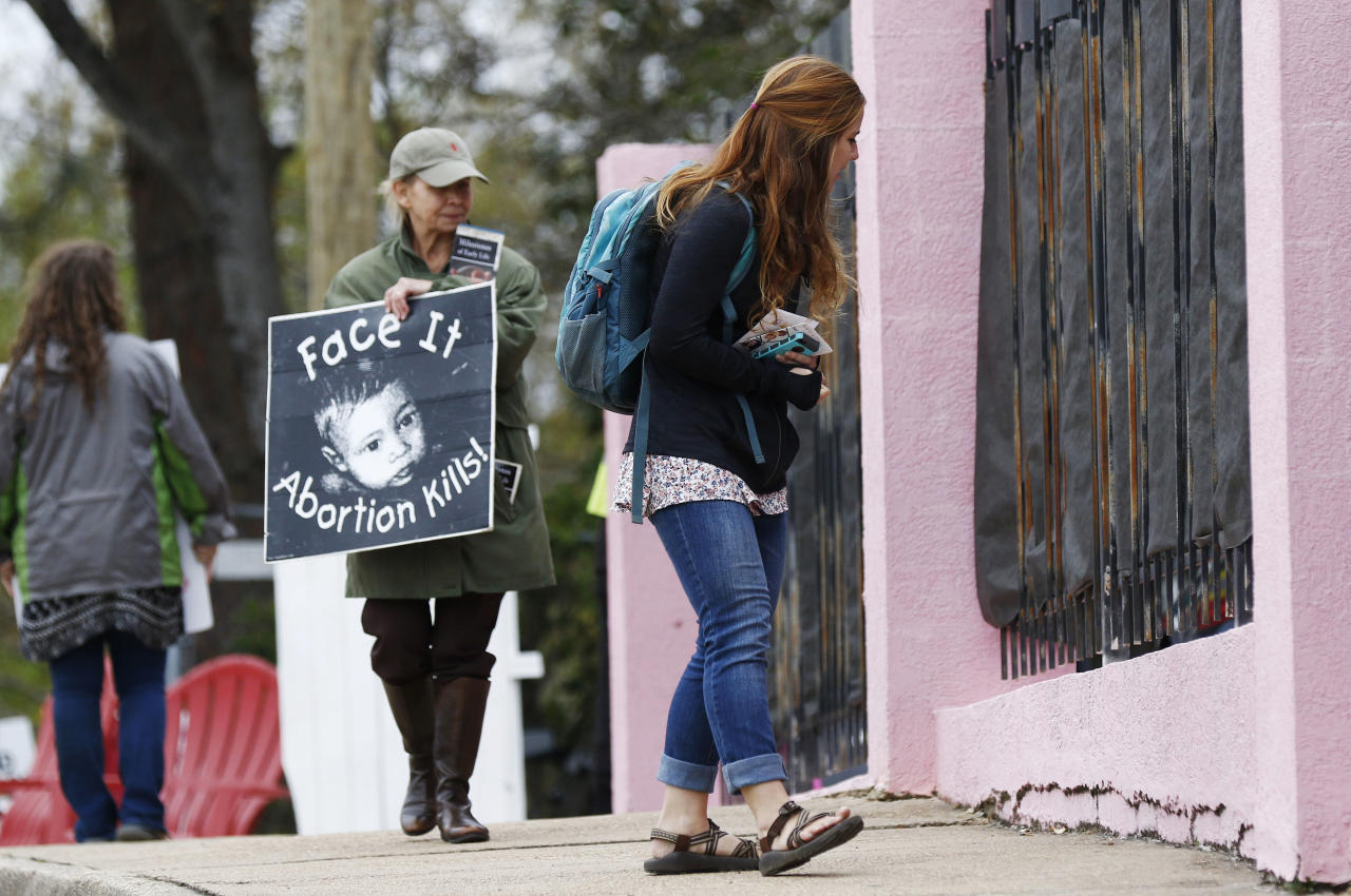 Anti-abortion sidewalk counselors Beka Tate, foreground, and Laura Duran, call out to a woman entering the Jackson Women's Health Organization's clinic, the only facility in the state that performs abortions, Tuesday, March 20, 2018, in Jackson, Miss. A federal judge is temporarily blocking a new Mississippi law that bans abortion after 15 weeks, the most restrictive abortion law in the United States. (AP Photo/Rogelio V. Solis)