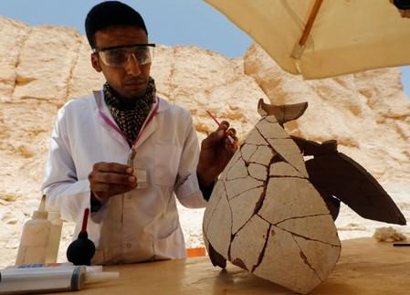 An Egyptian archaeologist works on objects discovered through an archaeological mission in the Monkey Valley near the Valley of the Kings in Luxor