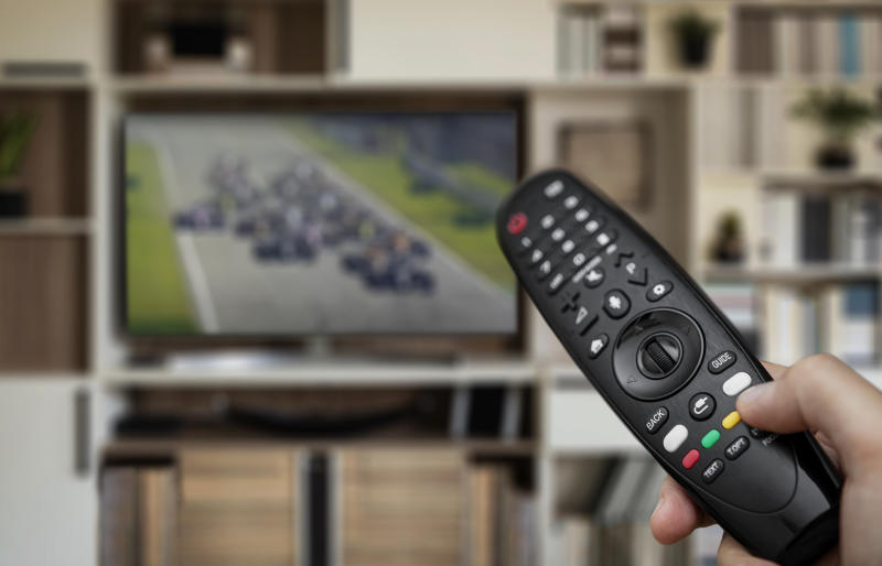 Hand holding remote control towards TV screen with car race placed on a wall unit