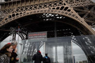 People walk past a screen announcing the closure of the Eiffel Tower after the French government banned all gatherings of over 100 people to limit the spread of the virus COVID-19, in Paris, Saturday, March 14, 2020. For most people, the new coronavirus causes only mild or moderate symptoms. For some it can cause more severe illness, especially in older adults and people with existing health problems. (AP Photo/Christophe Ena)