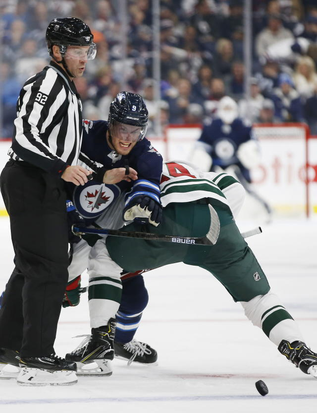 Winnipeg Jets' Andrew Copp (9) attempts to get past Minnesota Wild's Joel Eriksson (14) at a faceoff during the second period of an NHL hockey game Thursday, Oct. 10, 2019, in Winnipeg, Manitoba. (John Woods/The Canadian Press via AP)
