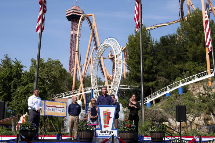 California Governor Gavin Newsom, center, welcomes the public to Six Flags Magic Mountain in Santa Clarita, Calif., on Wednesday, June 16, 2021. In the background are, Don McCoy, from left, President of Six Flags Magic Mountain, Michael Spanos, President of Six Flags, Los Angeles County Supervisor Kathryn Barger and state Sen. Henry Stern. Newsom continued his tour of the state after lifting most COVID-19 restrictions Tuesday. (David Crane/The Orange County Register via AP)