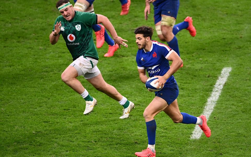 France's fly-half Romain Ntamack (R) runs with the ball during the Six Nations rugby union tournament match between France and Ireland at the stade de France, - AFP