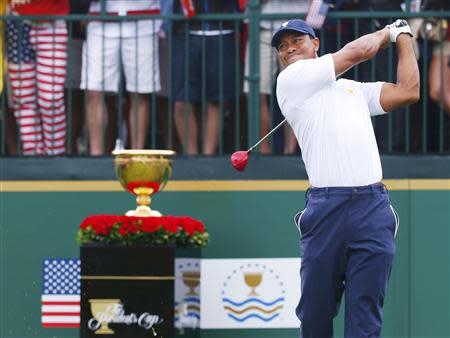 U.S. golfer Tiger Woods tees off on the first hole against International team member Richard Sterne of South Africa during the Singles matches for the 2013 Presidents Cup golf tournament at Muirfield Village Golf Club in Dublin