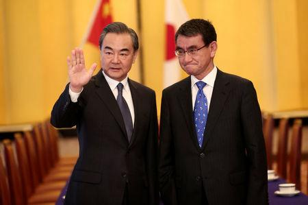 Chinese State Councilor and Foreign Minister Wang Yi (L) and Japan's Foreign Minister Taro Kono gesture at their meeting in Tokyo, Japan April 15, 2018. Behrouz Mehri/Pool via Reuters