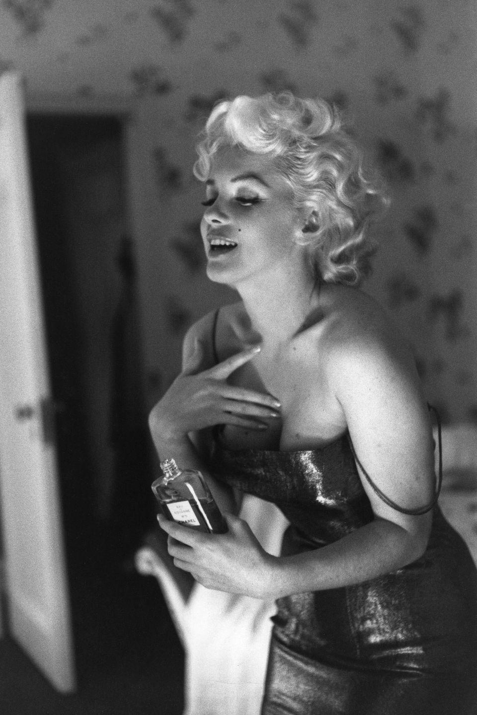<p>Monroe applies Chanel No. 5 perfume while getting ready in her room at the Ambassador Hotel to see the play <em>Cat On A Hot Tin Roof</em> in New York City. </p>