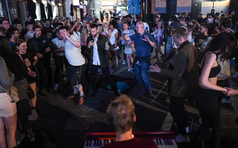 People dance in the streets on Saturday night before new restrictions come into force Monday, preventing groups of more than six from meeting - Peter Summers/Getty