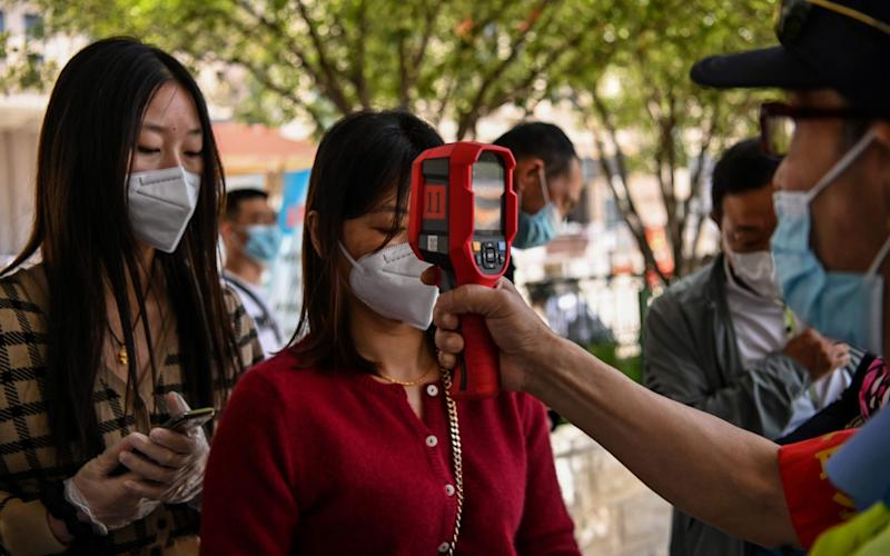 A worker wearing a face mask checks passengers' temperatures aafter their arrival at Hankou railway station in Wuhan - AFP