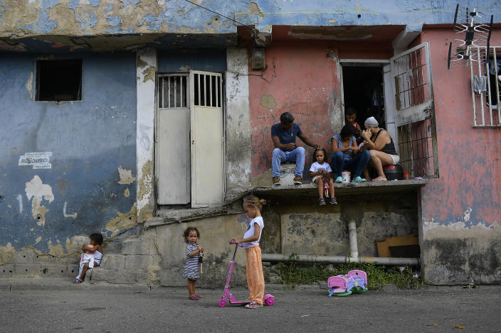 Girls play with their toys as their parents rest outside of their home in Petare neighborhood on Christmas Day in Caracas, Venezuela, Friday, Dec. 25, 2020, amid the new coronavirus pandemic. (AP Photo/Matias Delacroix)