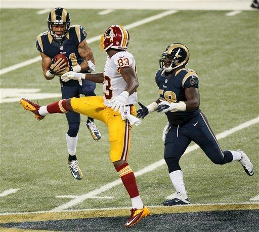 St. Louis Rams cornerback Cortland Finnegan, left, intercepts a pass intended for Washington tight end Fred Davis (83) as Rams linebacker Jo-Lonn Dunbar helps to defend on the play during the second quarter of an NFL football game on Sunday, Sept. 16, 2012 at the Edward Jones Dome in St. Louis. (AP Photo/St. Louis Post-Dispatch, Chris Lee) EDWARDSVILLE INTELLIGENCER OUT; THE ALTON TELEGRAPH OUT
