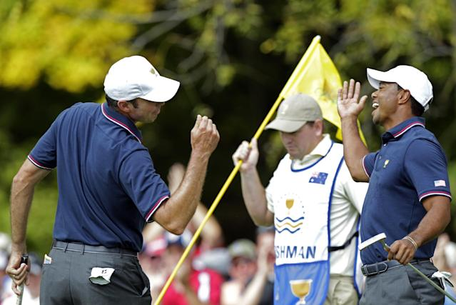 United States' Matt Kuchar, left, and teammate Tiger Woods celebrate Kuchar's birdie on the first hole during a four-ball match against the International team at the Presidents Cup golf tournament at Muirfield Village Golf Club Thursday, Oct. 3, 2013, in Dublin, Ohio. (AP Photo/Jay LaPrete)
