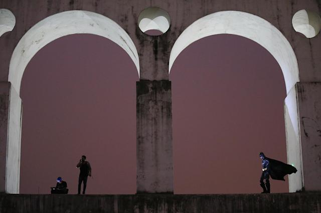 RIO DE JANEIRO, BRAZIL - OCTOBER 31: A protester (R) is dressed as Batman while standing at the Lapa arches on October 31, 2013 in Rio de Janeiro, Brazil. Protesters called for an end to police violence and corruption and voiced demands for better public services. (Photo by Mario Tama/Getty Images)