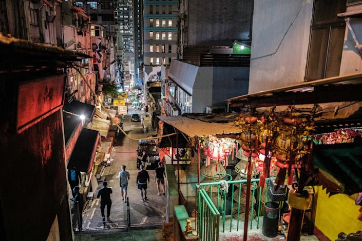 """Pedestrians walk on the usually busy Peel Street, popular for its restaurants and bars, in Hong Kong. The city's chief executive announced plans to temporarily ban the sale of alcohol in bars and restaurants as a measure to help stop the spread of the coronavirus. <span class=""""copyright"""">(Anthony Wallace / AFP / Getty Images)</span>"""