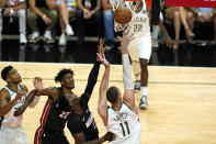 Milwaukee Bucks center Brook Lopez (11) shoots as Miami Heat forward Jimmy Butler (22) and center Bam Adebayo (13) defend during the second half of Game 4 of an NBA basketball first-round playoff series, Saturday, May 29, 2021, in Miami. (AP Photo/Lynne Sladky)