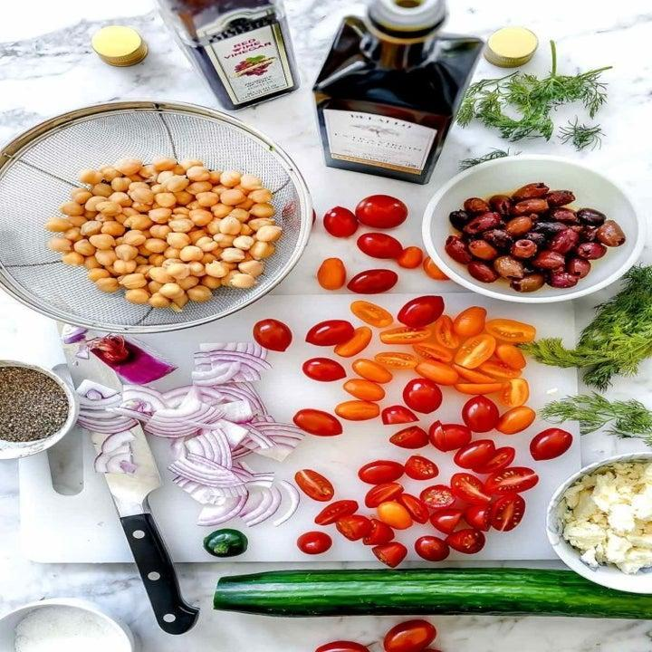 Chickpeas, tomatoes, cucumber, onion, and more ingredients for salad.