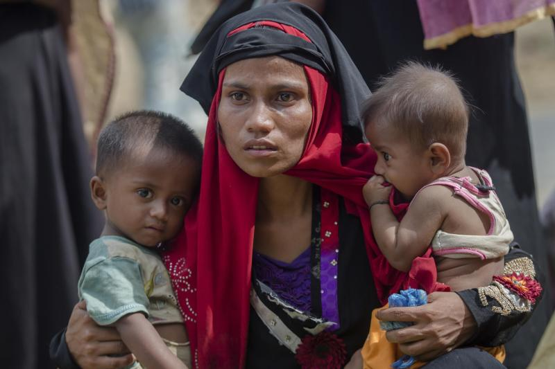 FILE - In this Oct. 22, 2017, file photo, a Rohingya Muslim woman, Rukaya Begum, who crossed over from Myanmar into Bangladesh, holds her son Mahbubur Rehman, left and her daughter Rehana Bibi, after the government moved them to newly allocated refugee camp areas, near Kutupalong, Bangladesh. Officials from the U.N. refugee agency and Bangladesh's government say few Muslim Rohingya refugees have responded to plans for their repatriation to Myanmar, and all who did say they don't want to go back. (AP Photo/Dar Yasin, File)