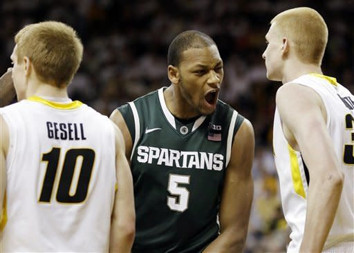 Michigan State center Adreian Payne (5) celebrates after scoring between Iowa's Mike Gesell, left, and Aaron White, right, during the first half of an NCAA college basketball game, Thursday, Jan. 10, 2013, in Iowa City, Iowa. (AP Photo/Charlie Neibergall)