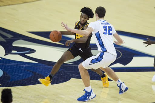 Kennesaw State's Spencer Rodgers, left, dribbles against Creighton's Ryan Kalkbrenner during the first half of an NCAA college basketball game in Omaha, Neb., Friday, Dec. 4, 2020. (AP Photo/Kayla Wolf)